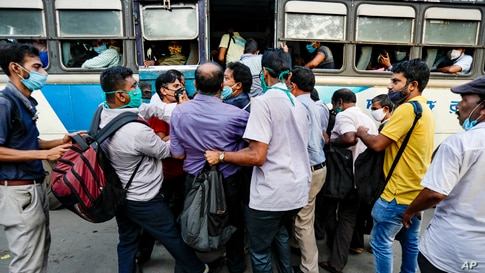 Commuters ignoring physical distancing norms push each other to board on a bus in Kolkata, India.