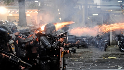 Police officers fire tear gas launchers during a clash with student protesters in Bandung, West Java, Indonesia.