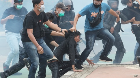 Plain-clothed police officers detain protesters during a rally in Jakarta, Indonesia.