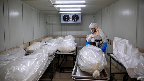 "A worker from ""Hevra Kadisha,"" Israel's official Jewish burial society, prepares bodies before a funeral procession at a special morgue for COVID-19 victims, Holon, near Tel Aviv."