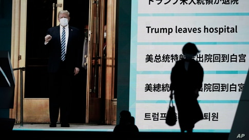 People walk past a screen in Tokyo, Japan, showing the news report that President Donald Trump has left a hospital to return to the White House after receiving treatments for COVID-19.