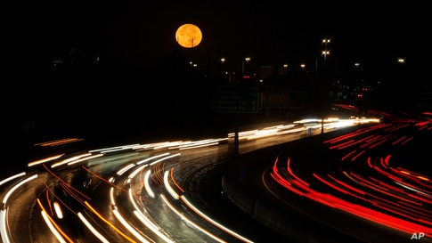 The full moon sets as morning traffic travels on a freeway in Leawood, Kansas.