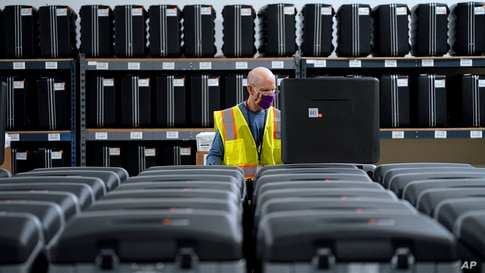 FILE - A worker prepares tabulators for the upcoming election, in Raleigh, North Carolina, Sept. 3, 2020. Early in-person voting starts Oct. 15, 2020, in all 100 counties in the battleground state.