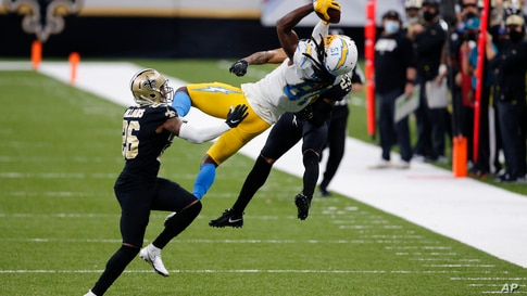 Los Angeles Chargers wide receiver Mike Williams (81) pulls in a pass between New Orleans Saints cornerback P.J. Williams (26) and cornerback Marshon Lattimore (23) in the second half of an NFL football game in New Orleans, Loisiana, Oct. 12, 2020.