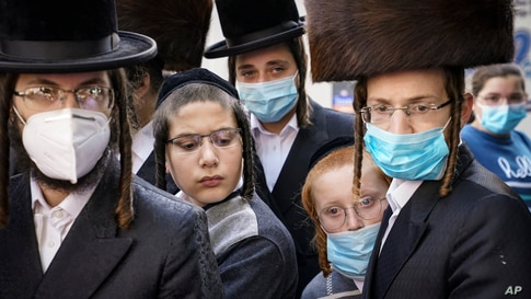 Members of Jewish Orthodox community gather around a journalist as he conducts an interview on a street corner, Oct. 7, 2020, in the Borough Park neighborhood of the Brooklyn borough of New York.
