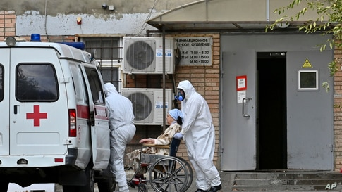 Medical workers wearing protective gear transport a patient suspected of being infected with the coronavirus from an ambulance to a hospital in Rostov-on-Don, Russia, Oct. 22, 2020.