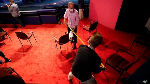 Members of the Commission on Presidential Debates use a measuring tape to ensure seats are socially distant as preparations take place for the vice presidential debate at the University of Utah in Salt Lake City.