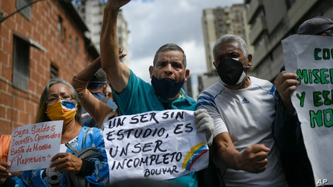"""A man shouts slogans as he holds the Spanish quote: """"An uneducated person is an incomplete person. Bolivar."""" during a demonstration by teachers demanding better salaries in Caracas, Venezuela, on World Teachers' Day."""