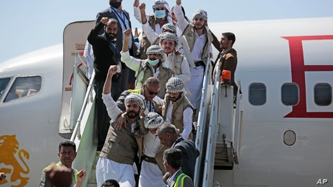 Yemeni prisoners chant slogans during their arrival after being released by the Saudi-led coalition at the airport in Sana'a.