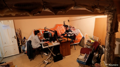 Radio journalists from a local public radio work at their studio located in a basement during the military conflict over the breakaway region of Nagorno-Karabakh, in Stepanakert.