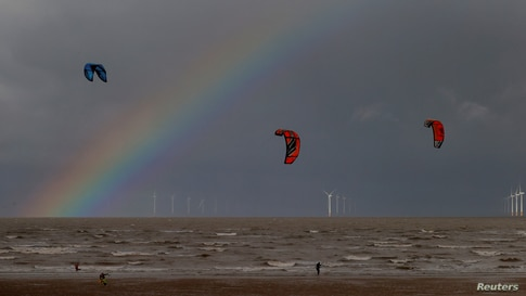 Kite surfers are pictured in front of the Burbo Bank offshore wind farm near New Brighton, Britain.