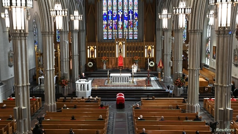 Mourners sit apart during the state funeral service for former Canadian prime minister John Turner at St. Michael's Cathedral Basilica in Toronto, Ontario.