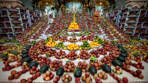 Priests arrange fruits offered by Hindu devotees inside a temple to mark the Annakut festival in Ahmedabad, India.