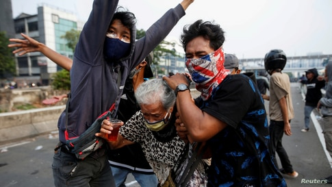 "Demonstrators cover an elderly woman during clashes with police, as they protest against the government's proposed labor reforms in a controversial ""jobs creation"" bill in Jakarta, Indonesia."