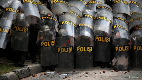 Police officers protect themselves with their shields during a protest against the new so-called omnibus law, in Jakarta, Indonesia.