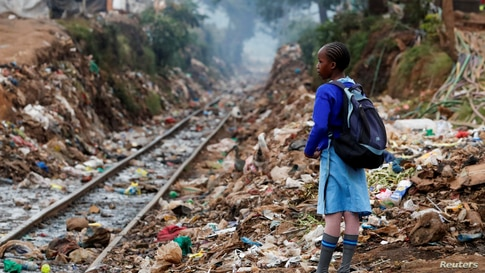 A schoolgirl stands next to the Kenya-Uganda railway line during the partial reopening of schools, due to the COVID-19 pandemic, in Kibera slums of Nairobi, Kenya.