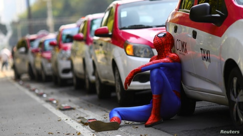 A person dressed up as Spider-Man sits next to a cab as taxi drivers hold a protest against taxi-hailing apps such as Uber, Cabify and Didi at Angel de la Independencia monument, in Mexico City, Oct. 12, 2020.