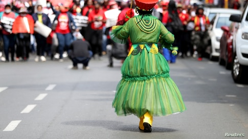 A Member of the Congress of South African Trade Unions (COSATU) joins others as they take part in a nationwide strike over issues including corruption and job losses, outside parliament in Johannesburg.