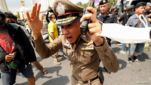 A police officer reacts during clashes between pro-democracy demonstrators and royalists during a anti-government protest on the 47th anniversary of the 1973 student uprising, in Bangkok, Thailand.