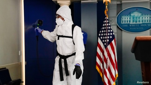 A member of the White House cleaning staff sprays the press briefing room in Washington, Oct. 5, 2020.
