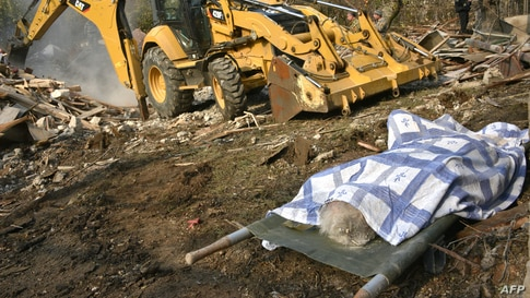 The body of a woman lays on a stretcher near a bulldozer clearing the debris of a destroyed house hit by shelling  during the…