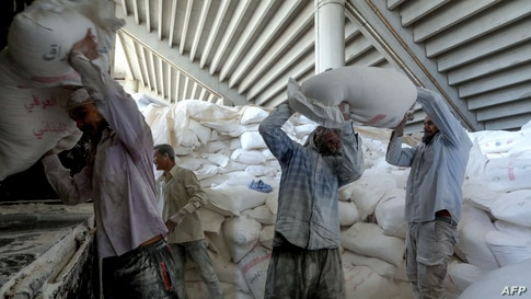 Workers load bags of flour donated by Iraq into trucks to remove them from their current storage under the Beirut Sports City…