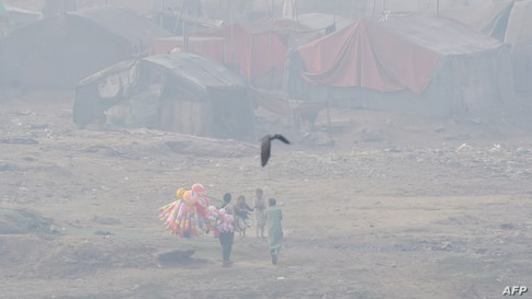 A vendor selling balloons looks for customers in a slum area amid heavy smoggy conditions in Lahore on November 13, 2020. …