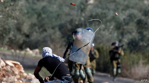 A Palestinian demonstrator uses a slingshot to hurl stones toward Israeli security forces during clashes with them following a…