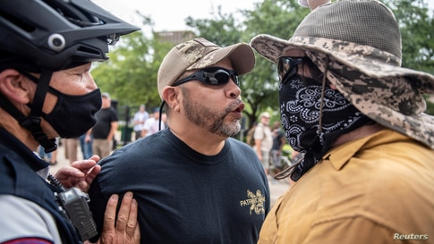 Two protesters at a protest against mandates to wear masks amid the coronavirus outbreak, Austin, Texas, June 28, 2020.