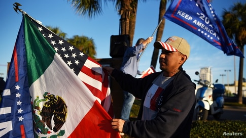 Jose Casares, 32, waves flags in support of Trump as voters line up at a polling station during Election Day in Houston, Texas.