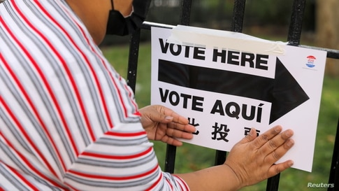 An election worker posts signage outside a polling station at the James Weldon Johnson Community Center on Election Day.