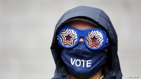 Cesia Kearns wearing glasses and a face mask is seen outside a polling place in the CenturyLink Field Event Center.