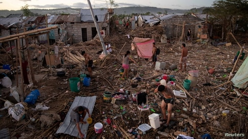 Residents bathe, wash, and pump water in their destroyed village following the damage caused by Typhoon Vamco, in Rodriguez,…