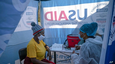 FILE - In this July 2, 2020 file photo, nurse Nomautanda Siduna, right, talks to a patient who is HIV-positive inside a gazebo…