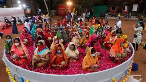 Indian women perform rituals standing inside an artificial pond on Chhat Puja festival in Mumbai, India, Friday, Nov. 20, 2020…