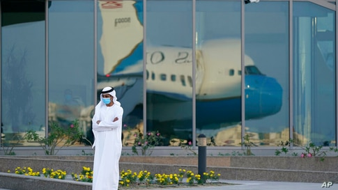 A man stands on a tarmac as Secretary of State Mike Pompeo's plane is reflected in windows at Al Bateen Executive Airport in…
