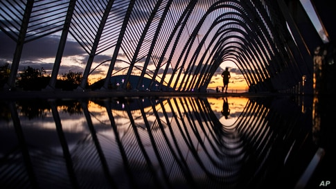 A man runs on a walkway of steel vaults, called the Agora, at the Athens Olympic Stadium complex as the sun sets, on Friday,…