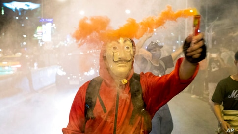 A protester wearing a mask holds a firework during a rally outside the headquarters of the Siam Commercial Bank, a publicly…
