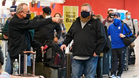 Travelers wait in line at the ticket counter before traveling from Cleveland Hopkins International Airport,  Nov. 25, 2020.
