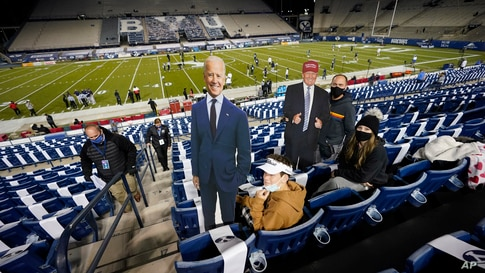 BYU fans hold up cardboard cutouts of Democratic presidential candidate former Joe Biden and President Donald Trump before an NCAA college football game between BYU and Western Kentucky, Oct. 31, 2020, in Provo, Utah.
