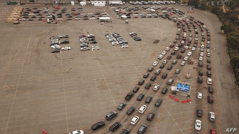 This aerial view shows people waiting in line in their cars at a Covid-19 testing site at Dodger Stadium in Los Angeles, California, Nov. 18, 2020.