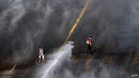 Demonstrators are sprayed by a riot police water cannon during clashes following a protest against Chilean President Sebastian Pinera's government in Santiago, Nov. 18, 2020.