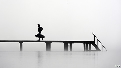 A man walks on a pier in heavy fog at lake Ammersee in Stegen, southern Germany.