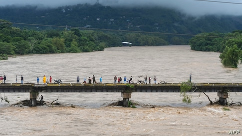 People watch the Humuya river flooding due to heavy rains caused by Eta Hurricane, in Santa Rita, Yoro department, 240 km northern Tegucigalpa, Nicaragua, Nov. 3, 2020.