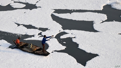 Men row a boat in the polluted waters of river Yamuna covered with foam in New Delhi, India.