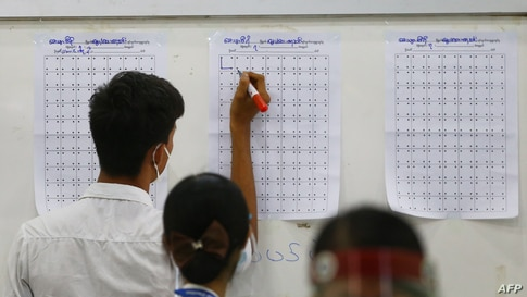 Election officials keep track of counted votes at a polling station after polls closed in Naypyidaw, Myanmar.