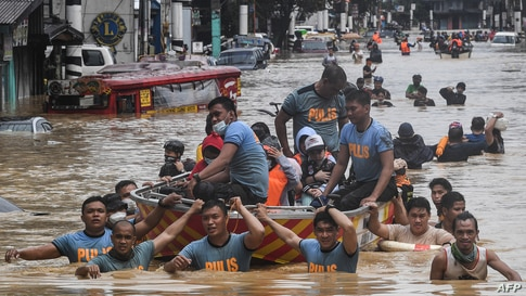 Rescuers pull a rubber boat carrying residents through a flooded street after Typhoon Vamco hit in Marikina City, suburban Manila, Philippines.