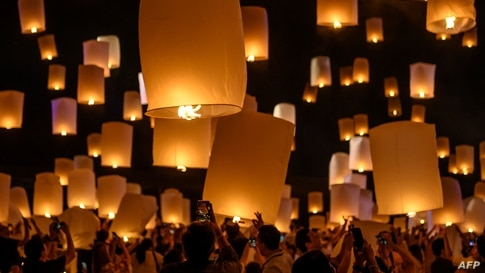 People light and release paper lanterns during the celebration of Loy Krathong festival outside Chiang Mai, Thailand, Oct. 31, 2020.