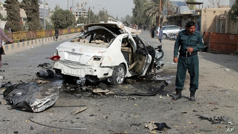 A policeman investigates a damaged car following a sticky bomb attack in Helmand province, southern Afghanistan, Nov. 12, 2020.