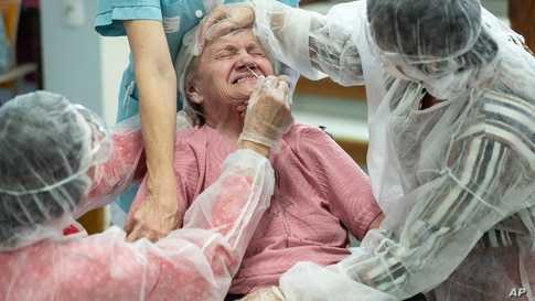 A woman is tested with a PCR COVID-19 test in a nursing home in Ammerschwihr, eastern France.